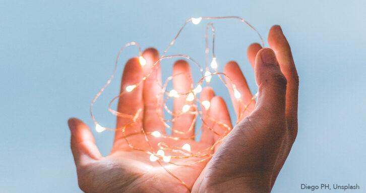 Hände berühren Lichterkette